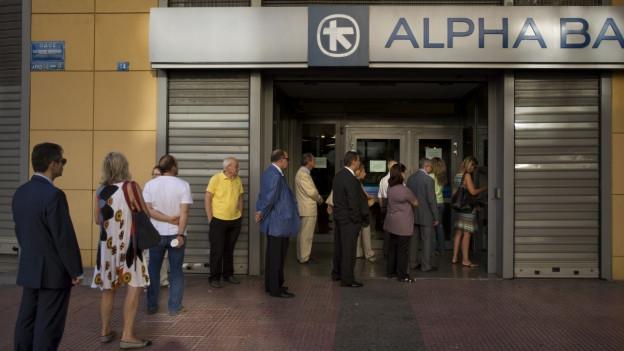 Griechinnen und Griechen stehen Schlange vor einem Bankomat, die Bank selber ist geschlossen.