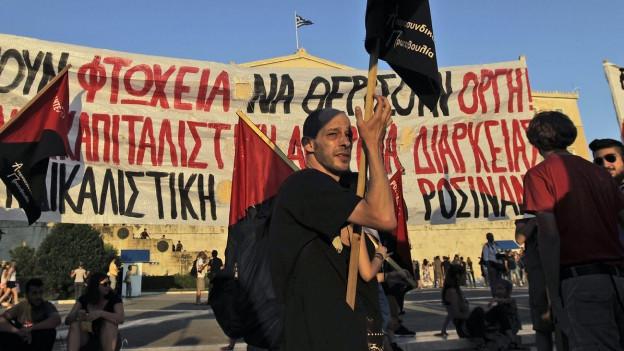 Ein Mann hält ein Transparent in die Höhe und protestiert gegen die beschlossenen Sparmassnahmen.