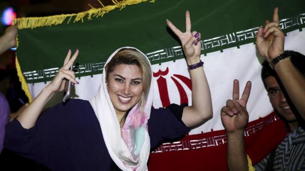 Eine Iranerin macht das Victory-Zeichen. Hinter ihr ist die iranische Flagge zu sehen.