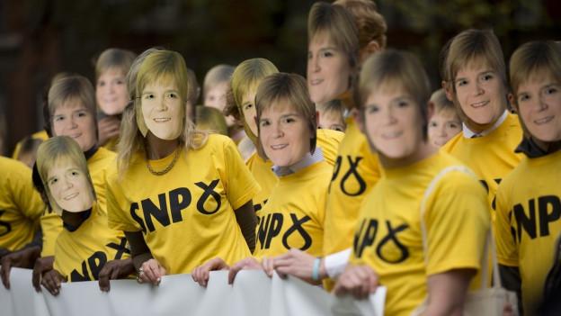 Anhänger der SNP tragen gelbe Shirts und Masken mit dem Konterfei von Nicola Sturgeon.