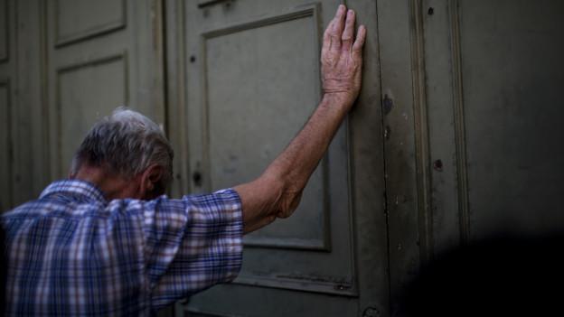 Ein alter Mann drückt an die geschlossene Tür einer Bank.