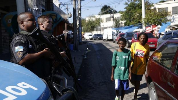 Aufnahme von zwei Militärpolizisten, die in einem Favela in Rio Dienst schieben. Zwei Jungen laufen an ihnen vorbei.