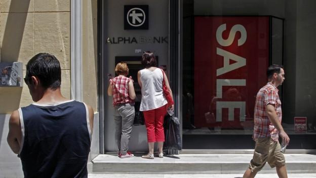 Auf dem Bild sind Menschen vor einem Geldautomaten in der griechischen Hauptstadt Athen zu sehen (13. Juli 2015). Nach drei Wochen öffnen am Montag im Land die Banken wieder.