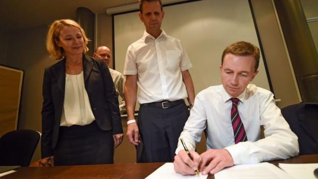 Lucke beim Unterschreiben, im Hintergrund schauen zwei Männer und eine Frau zu.