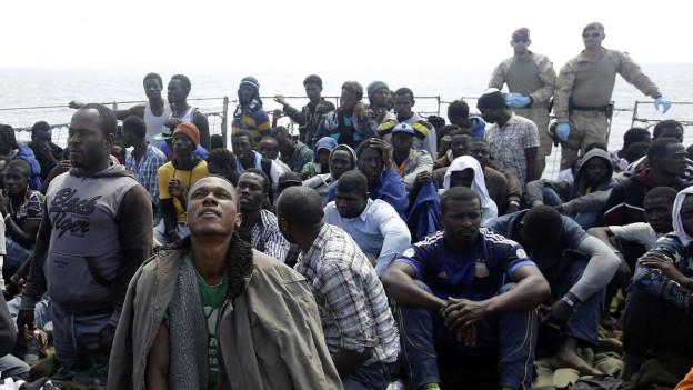 Auf dem Bild sind dutzende Flüchtlinge zu sehen, die in Sizilien auf einem Rettungsboot der EU Zuflucht gefunden haben.