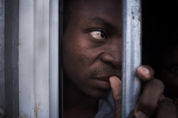 Ein illegaler Migrant in einem Käfig in Libyen