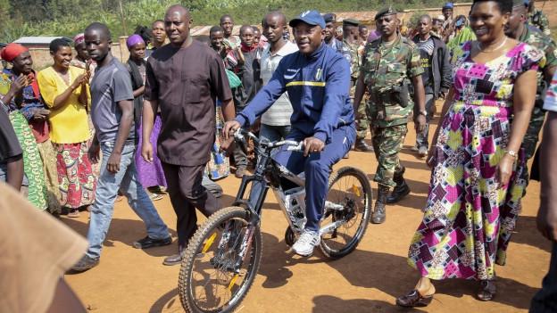 Burundis Präsident Pierre Nkurunziza auf dem Weg mit dem Fahrrad zur Wahlurne - rechts seine Drau, First Lady Denise Bucumi Nkurunziza