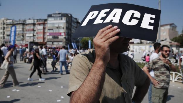Ein Demonstrant in Istanbul hält zum Schutz vor der Sonne ein «Peace»-Plakat auf