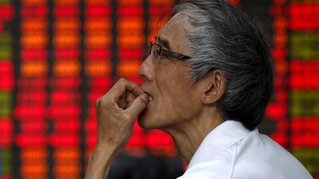 Ein Anleger studiert die Anzeigetafel an der Shanghaier Börse.