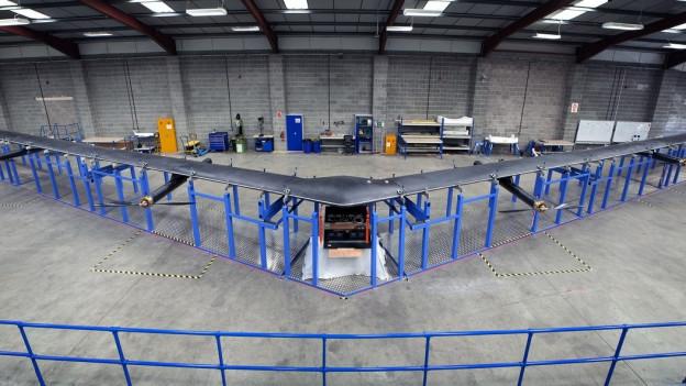In einer Lagerhalle hat Facebook ein Flugzeug fertiggestellt und beginnt jetzt mit der 30 Meter langen Drohne Flugtests