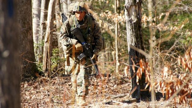 Ein Marineleutnant rennt bewaffnet durch den Wald von der Marineschule in Quantico