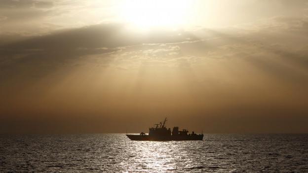 Ein Schiff der italienischen Küstenwache im Gegenlicht. Die Sonne ist über dem Meer am Untergehen.
