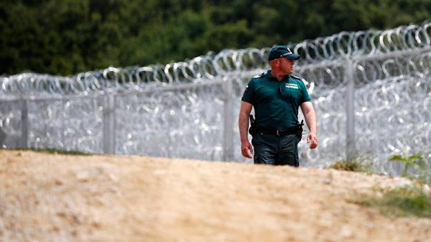 Ein bulgarischer Grenzpolizist kontrolliert die bulgarisch-türkische Grenze vor dem hochmodernen Stacheldrahtzaun.