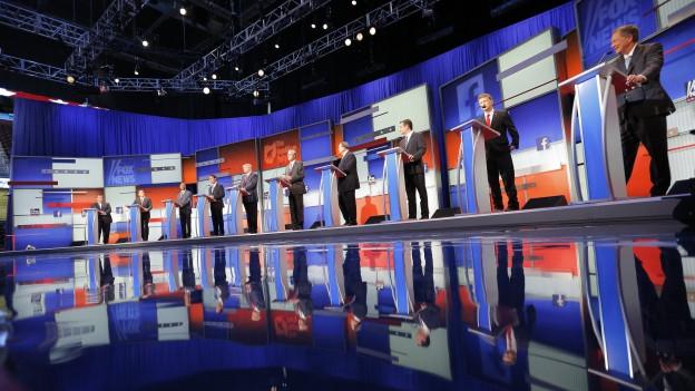 Fernsehstudio in den Farben der USA (blau, weiss und rot), an kleinen Rednerpulten stehen die Kandidaten.