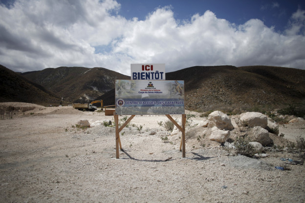 Einige Hügel, davor trockener Boden auf dem ein Schild steht mit der Aufschrift: «ici bientôt»