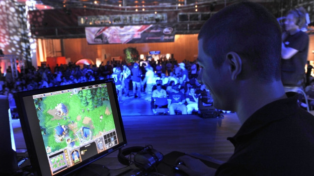 Ein Gamer blickt auf einen Computerbildschirm, im Hintergrund eine Menge Menschen in einer Halle, es ist ein Game-Turnier in Dresden 2009.