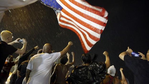 Menschen strecken Fäuste in die Luft vor US-Flagge.