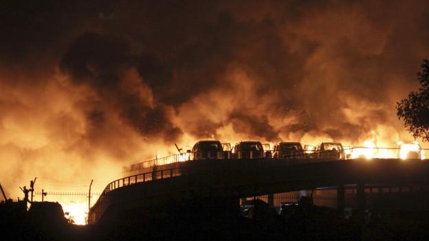 Zu sehen sind brennende Autos nach den Explosionen in einem Industriegebiet der chinesischen Millionenstadt Tjanjin. Augenzeugen berichteten, dass die Explosionen auch mehrere Kilometer entfernt zu spüren gewesen seien.