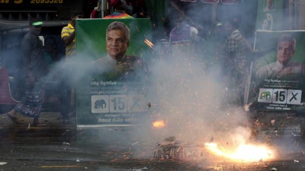 Ein Feuerwerkskörper explodiert vor Wahlkampfplakaten in Colombo.