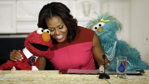Michelle Obama im Gespräch mit den Figuren Elmo und Rosita.