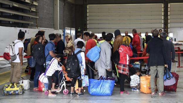Flüchtlinge stehen in einer Reihe vor einer Flüchtlingsunterkunft am Flughafen Wien-Schwechat.