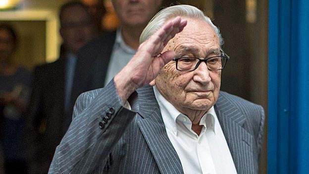 Egon Bahr hebt die linke Hand zum Gruss, gekleidet in einen grauen Anzug und mit weissem Hemd - ohne Krawatte.