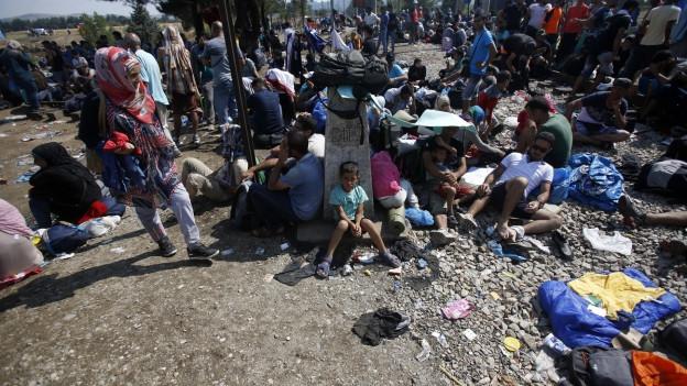 Das Bild zeigt viele Flüchtlinge, die rund um den Grenzstein an der mazedonischen Grenze warten - sitzend, liegend, stehend.
