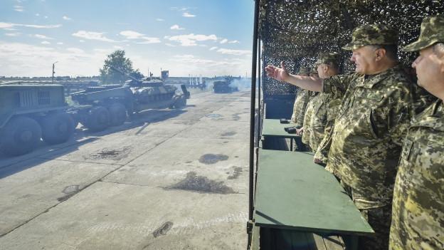 Zu sehen ist der ukrainische Präsident Poroschenko am vergangenen Samstag auf einem Luftwaffenstützpunkt in der Region Charkiw. Dort beobachtet er, wie bei einer Zeremonie neue Waffen und Fahrzeuge an ukrainische Soldaten übergeben werden.
