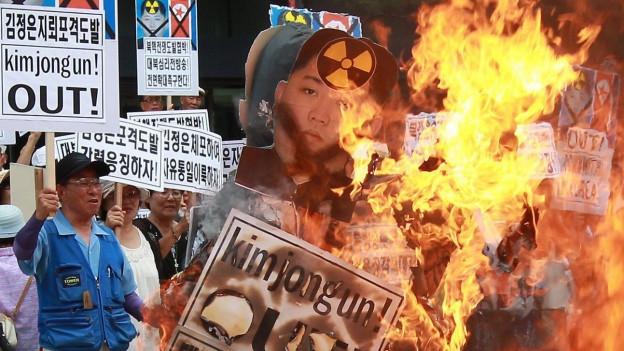 Aufnahme von demonstrierenden Südkoreanern, die Bilder des nordkoreanischen Machthabers Kim Jong-Un verbrennen.