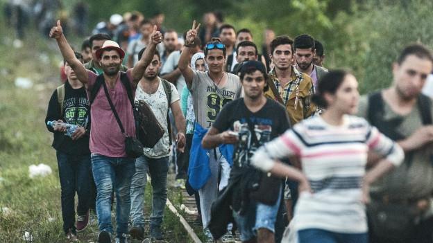 Aufnahme von Flüchtlingen, die auf Bahngleisen laufen und das V-Zeichen machen.