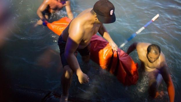 Drei Helfer ziehen Bodybag mit ertrunkenem Flüchtling aus dem Wasser.