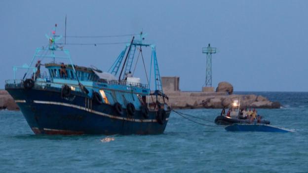 Zu sehen ist ein Fischkutter, das ein kleines Boot mit Flüchtlingen abschleppt.