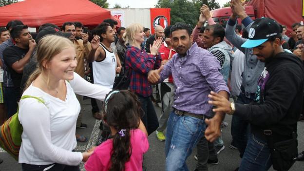 Flüchtlinge und Festbesucher amüsieren sich.