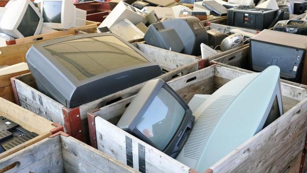 Das Bild zeigt ausrangierte Fernsehgeräte in grossen Holzkisten