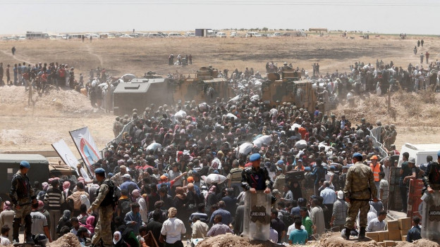 Grosse Menschenmenge in Wüstenlandschaft.