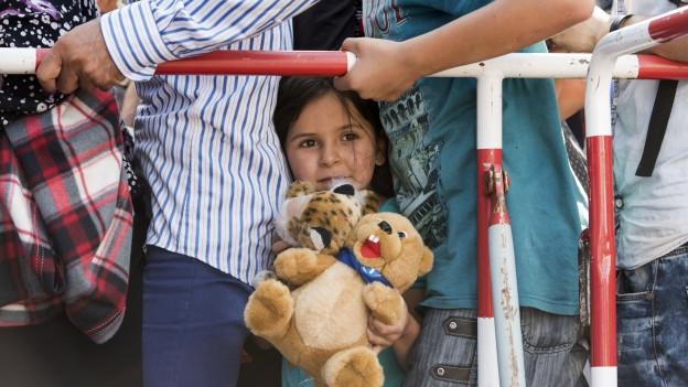 Kleines Mädchen mit Teddybär in einer Menschenschlange.