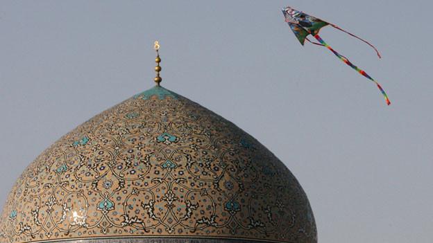 Symbolbild. Ein Drache fliegt über die Kuppel einer Moschee in Isfahan, Iran.