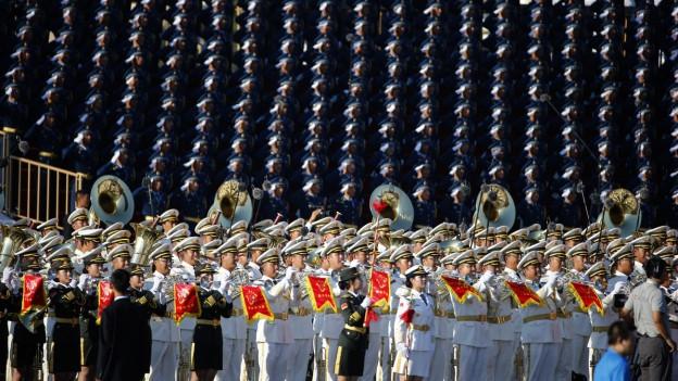 Männer in weissen Uniformen mit Instrumenten spielen in einer Militär-Band.