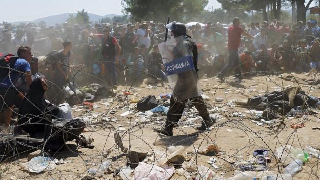 Ein Polizist steht vor dutzenden Flüchtlingen an der Grenze.