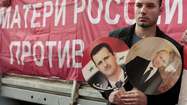 Ein Demonstrant hält Bilder von Wladimir Putin und Bashar al-Assad in die Höhe. Im Hintergrund ein Banner mit der Aufschrift «Mutter Russland gegen Krieg».