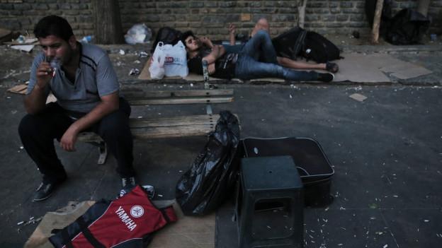 Ein Mann sitzt auf einem kleinen Holzbänkchen und raucht eine Zigarette, im Hintergrund liegen zwei weitere Männer auf Kartons.
