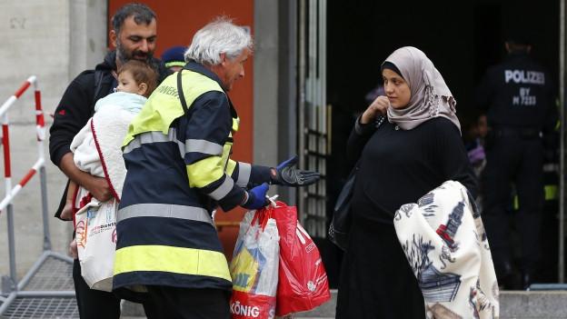 Eine Frau in schwarzem Kleid un Kopftuch kommt aus einem Bahnhofsausgang, ein Helfer mit gelber Weste geht auf sie zu.
