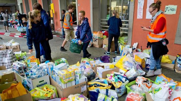 Zu sehen sind Helferinnen und Helfer am Hauptbahnhof München, die dort Hilfsgüter für ankommende Flüchtlinge sortieren.
