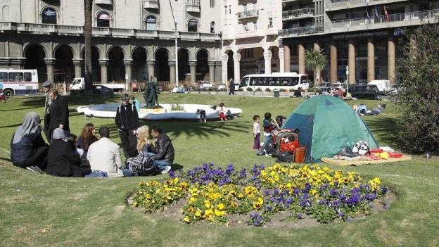 Syrische Füchtlinge sitzen vor ihrem Zelt auf einer Wiese.