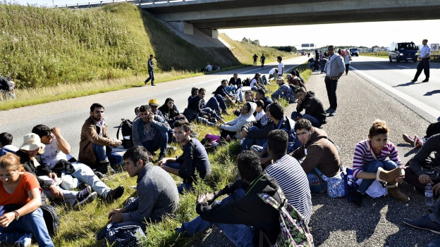 Aufnahme einer Gruppe von Flüchtlingen, die auf einer Autobahn sitzen.