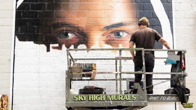 Aufnahme von einem Maler auf einer Hebebühne, der ein Werbebild malt.