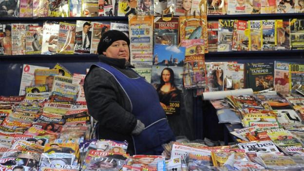 Aufnahme einer Kioskfrau in Russland, die inmitten vieler Magazine und Zeitungen sitzt.