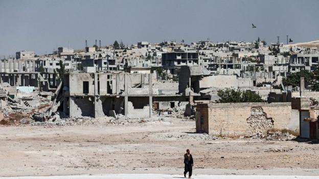 Aufnahme eines Mannes, der vor zerstörten Häusern vorbeiläuft.