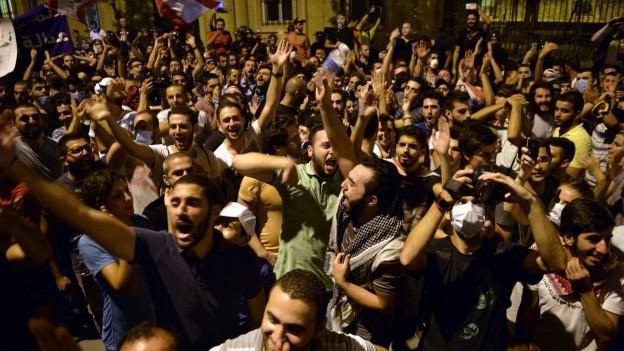 Menschen protestieren in den Strassen Beiruts.