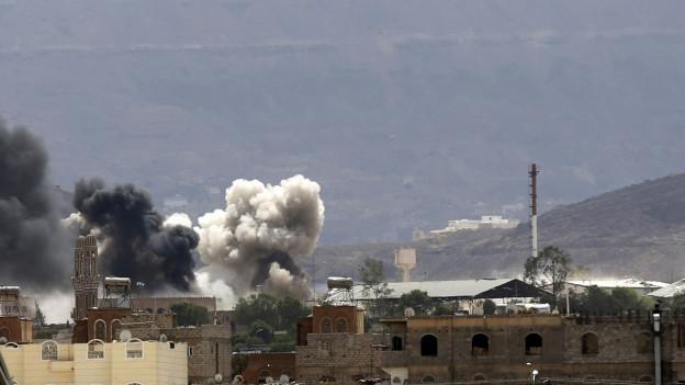 Nach einem Bombeneinschlag steigt Rauch über mehreren Häusern auf.